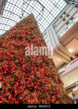 Large Artificial Christmas Tree at the Eaton Centre: A huge, perfectly conical tree decorated with red and white lights is a Christmas center pieces in this busy toronto mall. - Stock Image