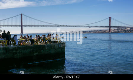 Lisbon, Portugal - March 2nd, 2019: People relax in outdoor restaurant terrace overlooking the iconic 25 April bridge in Lisbon, Portugal - Stock Image