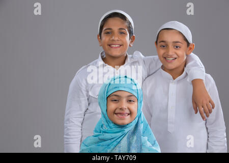 two brothers standing with their sister in front - Stock Image
