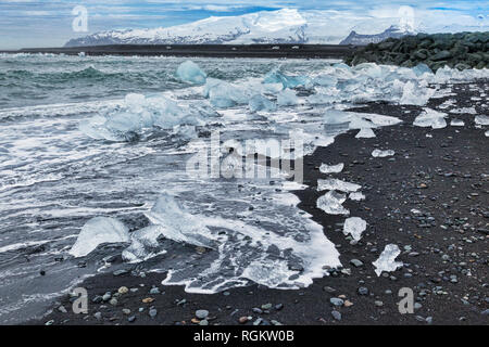 Diamond Beach, South Iceland, where ice from the Jokulsarlon Glacial Lagoon washes up on the black sand beach. - Stock Image