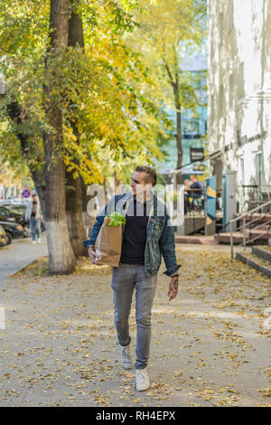 Man carrying groceries on autumn sidewalk - Stock Image