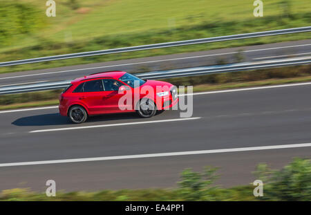 A red saloon car speeding along a motorway. Motion blur used to give a sense of speed. - Stock Image