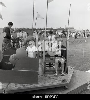 1960s, historical, children on a wheel at a outside fete, England, UK. - Stock Image