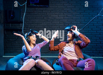 Happy man and woman giving five each other after the game in virtual reality in the playing room - Stock Image