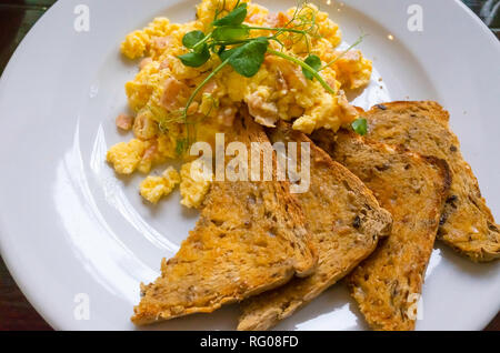 Breakfast brunch or early lunch in a café scrambled egg with smoked salmon and multi grain toasted bread and water cress garnish - Stock Image