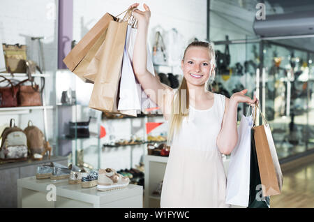Happy girl customer is showing purchases in fashion boutique - Stock Image