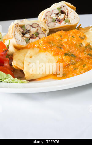 Mexican Chicken and re-fried bean Chimichanga with tomato salsa and hot chili sauce - Stock Image