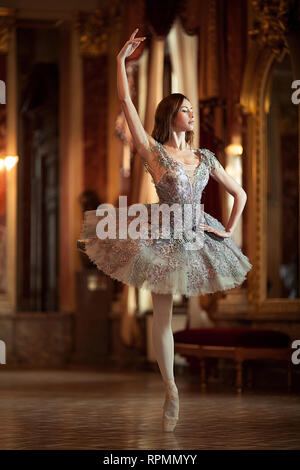 Beautiful ballerina dancing in a hall against the luxurious interior. Arabesque ballet pose. - Stock Image