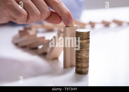 Close-up Of A Businesswoman's Hand Stopping The Wooden Blocks From Falling On Stacked Coins - Stock Image