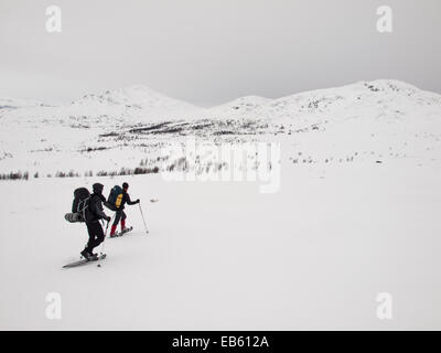 two men with heavy packs  snowshoeing through a winter mountain landscape with with sparse trees and mountains - Stock Image