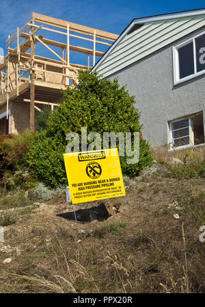 Warning sign by Kinder Morgan at a residential construction site alerting to the dangers of the underground high pressure pipeline. - Stock Image