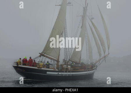 Two masted Schooner with sails on portside tack sails through fog - Stock Image