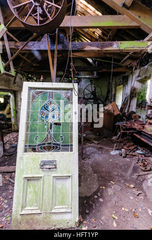 Door with stained glass window in an old shed workshop with rusty tools - Stock Image