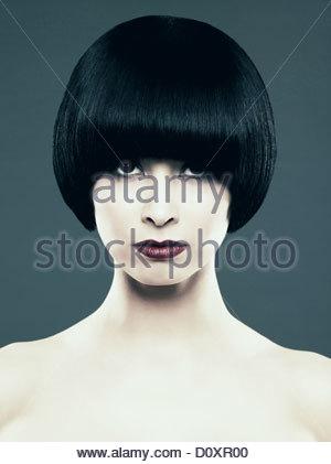 Young woman with black bob looking at camera - Stock Image