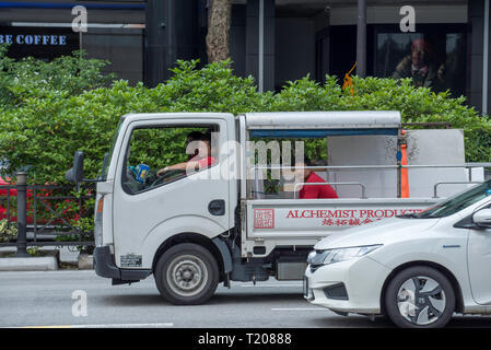 A work truck waits in Singapore traffic with two people in front seats and a third person in the back tray - Stock Image