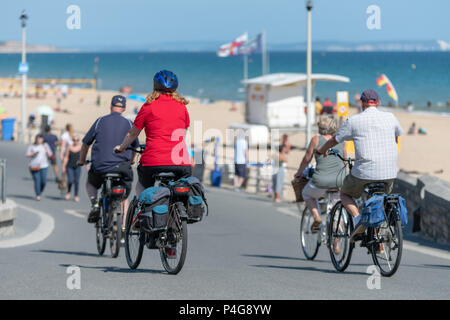 Bournemouth, UK. 22nd June 2018. UK sunny weather, four adults cycle along the seafront at Boscombe beach in Bournemouth. Thomas Faull/Alamy Live News - Stock Image