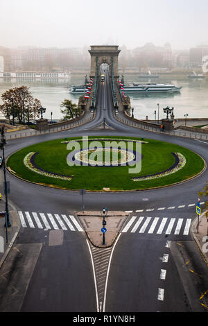 Budapest, Hungary - Clark Adam Square and Szechenyi Chain Bridge with cruise ship on River Danube on a foggy autumn morning - Stock Image