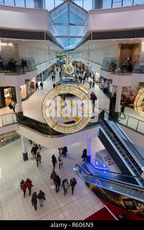 Christmas decotrations in Buchanan Galleries, a shopping mall in the centre of Glasgow, Scotland. Shoppers are  seen on three levels of the mall. - Stock Image