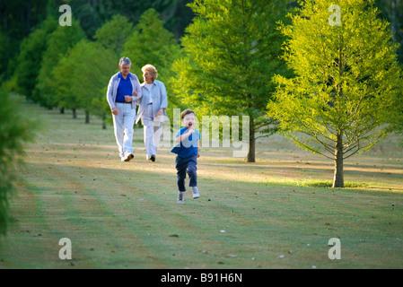 Grandparents walking and grandson running - Stock Image