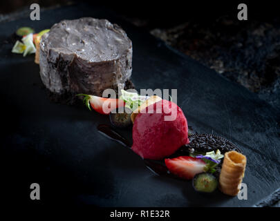 Oreo Cheesecake on a dark slate background with strawberry sorbet - Stock Image