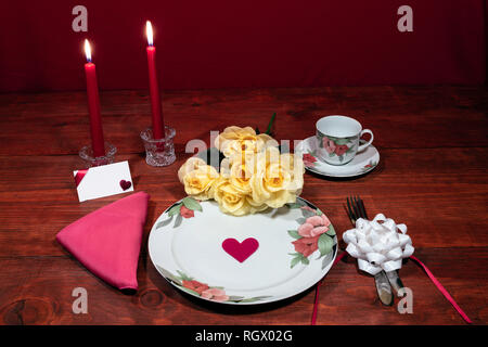 Floral pattern fine china dinnerware with matching plate, cup and saucer. bouquet of yellow roses, pink napkin, silverware, red candles and card - Stock Image
