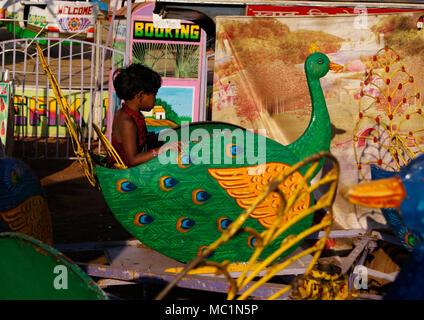 Indian Girl Child enjoying peacock ride in Children's Park Odisha India - Stock Image