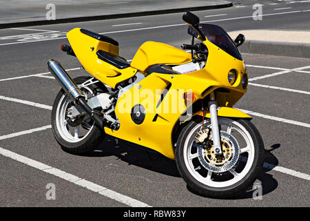 A bright yellow sports style Honda motorcycle in Melbourne Docklands,Victoria Australia. - Stock Image