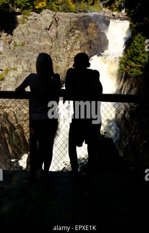 Couple in silhouette at viewpoint looking at raging torrent of water plunging down gorge Canyon Ste Anne River Park - Stock Image