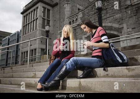 Two female college students sitting on the steps of a building texting on the cell phones, University of British Columbia, - Stock Image