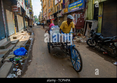 Poverty in Chennai, India, where a man cycles  bottles of water along a quiet side street - Stock Image