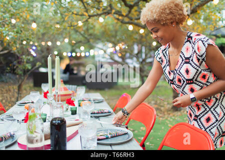 Woman setting table for dinner garden party - Stock Image