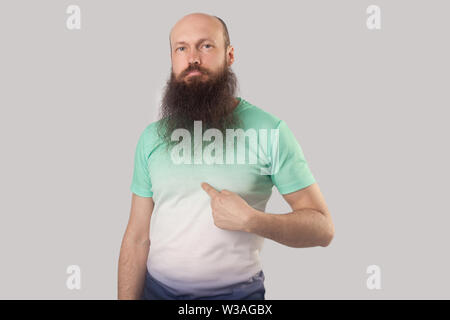 This is me! Portrait of confident middle aged bald man with long beard in light green t-shirt standing, pointing himself and looking with proud face. - Stock Image