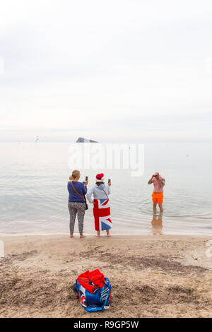 Benidorm, Costa Blanca, Spain, 25th December 2018. British tourists dress for the occasion on Christmas Day in this favourite getaway destination for Brits in mediterranean hotspot. A man coming out of the sea in orange shorts with women taking pictures in a union jack towel. - Stock Image