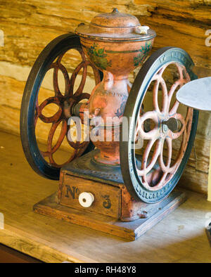 Coffee Grinder number 3: An old iron, hand cranked coffee grinder on display at the Cumberland Village musuem general store. - Stock Image