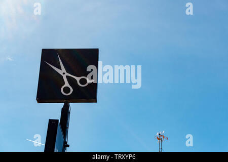 A pair of  scissors against a black background hairdressers sign against a blue sky - Stock Image