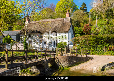A picturesque thatched cottage and footbridge in Helford, Cornwall, England - Stock Image