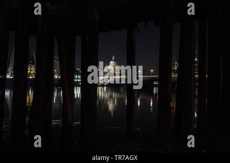 St Paul's Cathedral at dawn, photographed from the banks of the River Thames under an old victorian wooden pier, London, England, UK - Stock Image