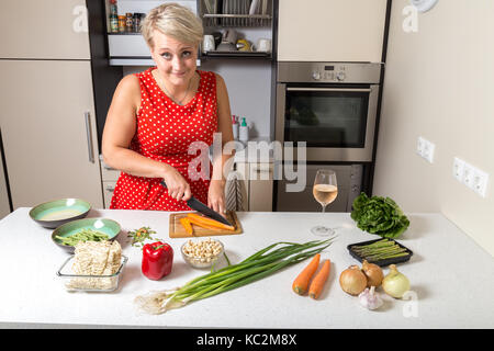 Girl smiling at camera and preparing food - Stock Image