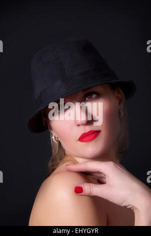 Glamour portrait of beautiful sexy young female woman with red lips on black background - Stock Image