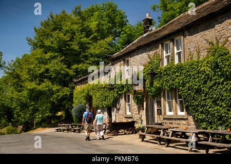 UK, Yorkshire, Wharfedale, Appletreewick, senior walkers passing Craven Arms public house - Stock Image