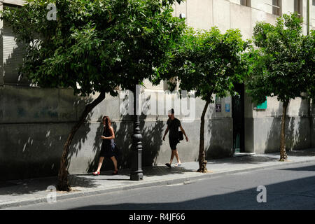 People walking in the shade in Seville, Spain. August 2018 Temp 43 degrees​. - Stock Image