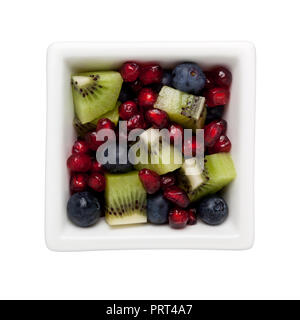Pomegranate arils, blueberries and diced kiwifruit in a square bowl isolated on white background - Stock Image
