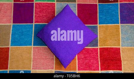 Purple covered cushion on a multi coloured squared rug. - Stock Image