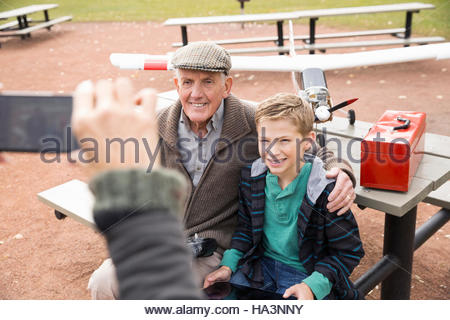 Woman with camera phone photographing father and son with model airplane in park - Stock Image