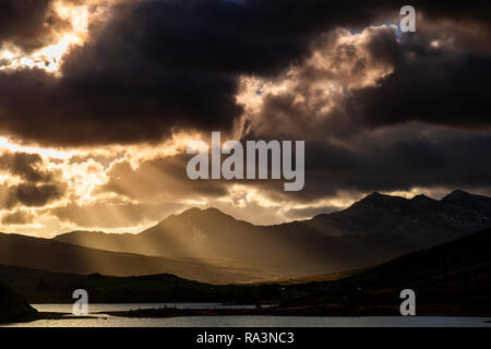 Snowdon mountain with sunbeams and clouds, Snowdonia, North Wales - Stock Image