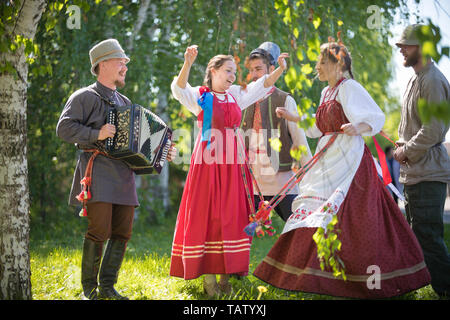 People in traditional Russian clothes are dancing in the woods - one of them plays the accordion and singing - gorizontal view - Stock Image