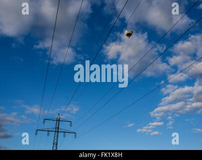 Balloon flying high above power line, Celle, Lower Saxony, Germany - Stock Image