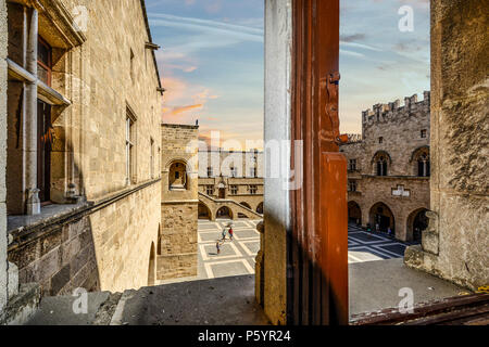 View from a window as tourists walk the courtyard of the Palace of the Grand Master of the Knights of Rhodes on the island of Rhodes Greece - Stock Image