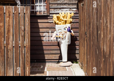 Milan , Italy 17 July 2018 : an abandoned statue that represents the advertising of a fries shop . French fries mascots are the favorite side dish and they pair on many hamburgers - Stock Image