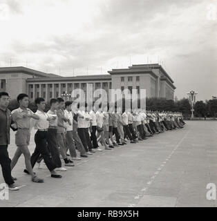 1960s, Beijing, China, large group of young chinese men wearing civilian clothiing doing military type marhcing exercises in Tiananmen square outside the 'Great Hall of the People', the People's National Congress building, the Chinese Parliament. The are preparing for 'National day', which celebrates the end of the Chinese civil war and the establishment of the People's Repubic under Chairman Mao Zedong. - Stock Image